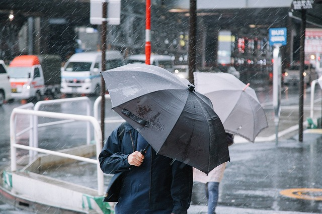 台風で傘さす人